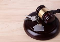 Concept for real estate auction or law.  A hardwood gavel laying on a sound block next to a metallic key ring in the shape of a house.