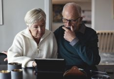 Senior couple using digital tablet while sitting by dining table in living room