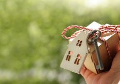 house and key tied to a gift in hand against a background of blurry green spaces on a sunny day