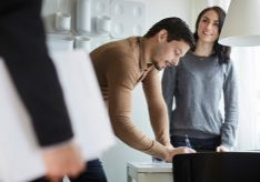Woman looking at real estate agent while man signing documents at new home