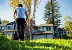 Young man mowing the lawn.Low angle shot / self portrait. Neighborhood setting.Shallow depth of field.