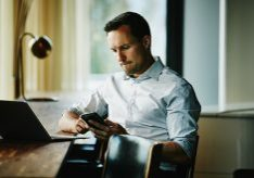 Businessman looking at smartphone while sitting at counter in office coworking space working on project on laptop